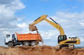 stock photo of dump_truck  - Excavator loading sand in rear - JPG