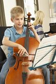 Boy and girl playing cello and  piano at home