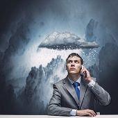 Businessman sitting under rain talking on mobile phone