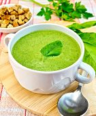 Soup Puree With Spinach Leaves And Spoon On Fabric