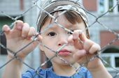 Unhappy Boy Behind Bars
