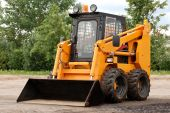 stock photo of skid-steer  - small yellow skid steer loader bulldozer outdoors - JPG