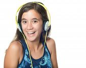 Beautiful hispanic teenager listening to music on her headphones and laughing isolated on white