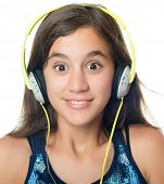 Beautiful hispanic teenager listening to music on her headphones isolated on white