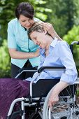 Nurse Hugging Woman On A Wheelchair