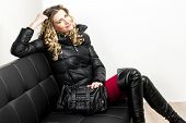 woman wearing fashionable clothes sitting with a handbag on a sofa