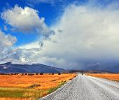 Strong wind drives the clouds. The dirt road in the endless pampas. On the horizon, the mountains v