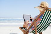Woman in sunhat sitting on beach in deck chair using tablet pc on a sunny day
