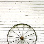 picture of wagon wheel  - An old antique wooden wagon wheel is leaning up against a white rustic wall background with peeling paint - JPG