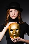 Redhead woman in hat  iwith mask in hypocrisy consept against dark  grey background