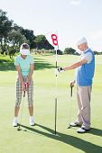 Golfer holding eighteenth hole flag for partner putting ball on a sunny day at the golf course