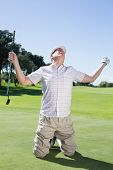Kneeling golfer cheering on putting green on a sunny day at the golf course