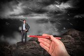 Composite image of hand drawing businessman against large rock overlooking snowy sky