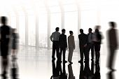 Composite image of business colleagues standing against room with large window looking on city