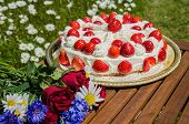 Summer Flowers At A Table With A Homemade Strawberry Cake