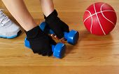 image of lifting-off  - Horizontal image of female hands wearing workout gloves while lifting small weights off of wooden gym floor with red ball and shoe in background - JPG