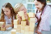 Three little friends playing with wooden bricks at leisure