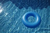 Floating Inner Tube In A Pool With Waves Reflecting In The Summer Sun