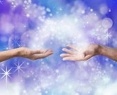 stock photo of shaman  - Man and woman both with one hand each palm up with an arc of white light and sparkles joining them on an electric blue colored energy formation background - JPG