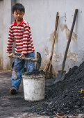 Boy Scoops Coal In Bucket.