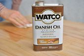 DNEPROPETROVSK, UKRAINE - MAY 30, 2014: Man applying the Watco Danish oil to the wood. Watco is one
