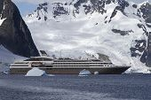 Tourist Liner Sailing Among Icebergs In Antarctica On A Background Of Mountains