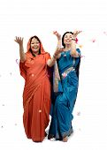 image of dancing rain  - Two mature women in sari dancing under rain of flowers on white background - JPG