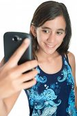 Hispanic teenage girl taking herself a photo with her mobile phone isolated on white