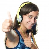 Beautiful hispanic teenager listening to music on her headphones while doing a thumbs up sign isolat