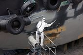 Man Spray Painting Hood Of Ship
