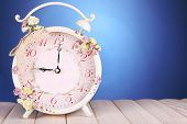 Beautiful vintage alarm clock with flowers on wooden table, on blue background