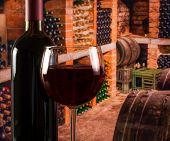 Red Wine Glass Near Bottle On Old Wine Cellar Background With Space For Text