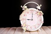 Beautiful vintage alarm clock with flowers on wooden table, on black background