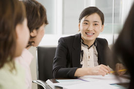 image of business meetings  - A group of women are seated aroung a desk in a business meeting and looking at each other - JPG