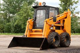 stock photo of skid-steer  - small yellow skid steer loader bulldozer outdoors - JPG
