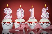 Happy New Year For 2015 Red Velvet Cupcakes In Red And White Theme With Lit Candles On A Red Backgro