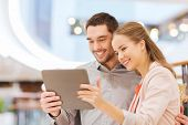 shopping, technology and people concept - happy couple with tablet taking selfie in mall or business center