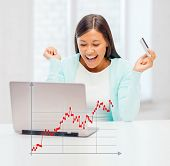 banking, business, finances and happy people concept - laughing businesswoman with laptop, credit card and forex graph