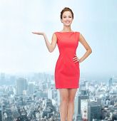 advertising, holidays and people concept - smiling young woman in red dress holding something on palm of her hand over city background