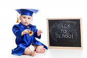 funny baby with bell in academician clothes at chalkboard