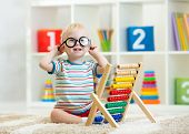 child toddler with eyeglasses playing abacus