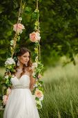 Beautiful bride swinging on the swings in the Park.