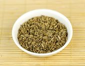 picture of cumin  - Cumin seeds in bowl against wooden background - JPG