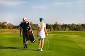 pic of sportive  - Young sportive couple playing golf on a golf course walking to the next hole - JPG