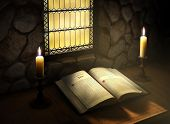 stock photo of stained glass  - Open Bible flanked with two candles near a sunlit stained glass window in an old monastery - JPG