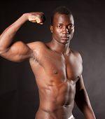 Beautiful and muscular black man in dark background