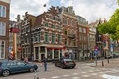 People And Cars On A Typical Intersection In Amsterdam