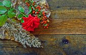 Red Rose And Foliage On Wooden Table