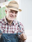 picture of dungarees  - Smiling cheerful farmer posing in checked shirt and dungarees - JPG