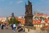 Beggar And Tourists On The Charles Bridge In Prague